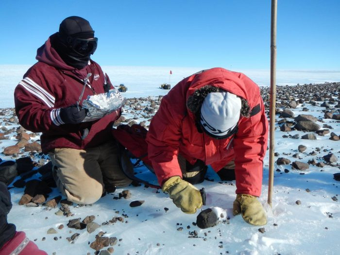 Researchers on hands and knees examining rocks