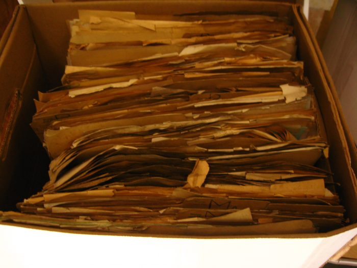 Damaged documents in cardboard file boxes