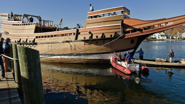 People in dhingies examine wooden ship replica