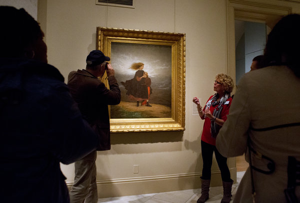 Vistors listen while docent talks about painting.
