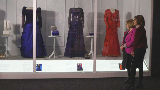 Two women in front of display case featuring inaugural gowns
