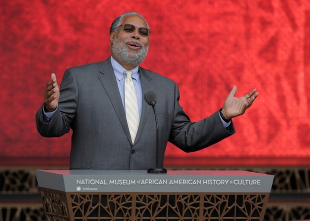 Lonnie Bunch at podium against red background