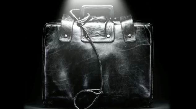 Still from film showing leather satchel