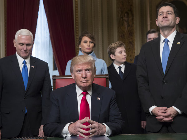 Trump sits at desk surround by family and politicians