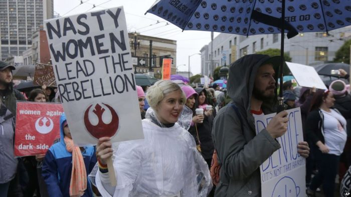Woman dressed as Princess Leia holding sign