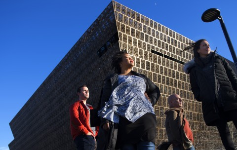 Group stands in front of museum; shot from below