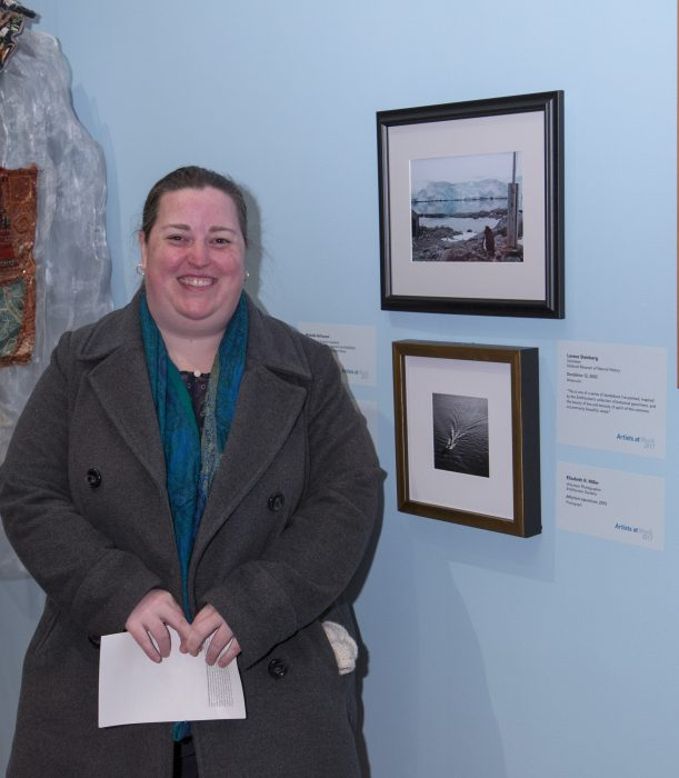 Artist stands next to her work in gallery