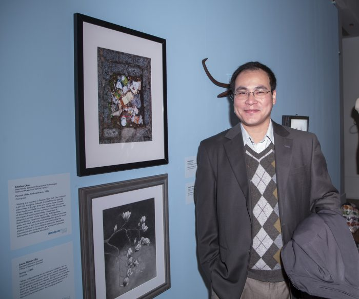 Artist with his work in gallery exhibition.