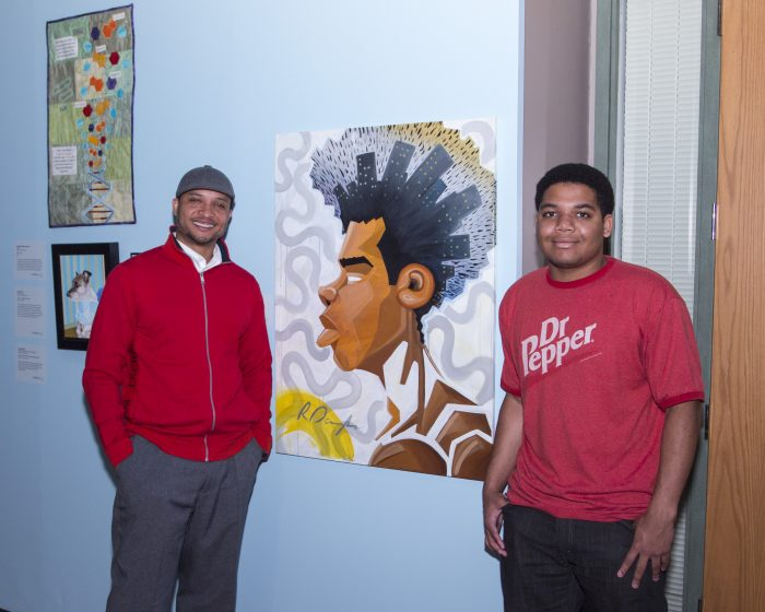 Artist and young man stand next to painting in exhibition gallery