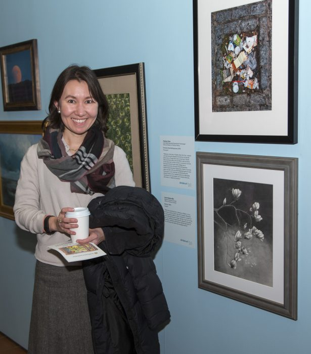 Artists standing with her work in gallery exhibition