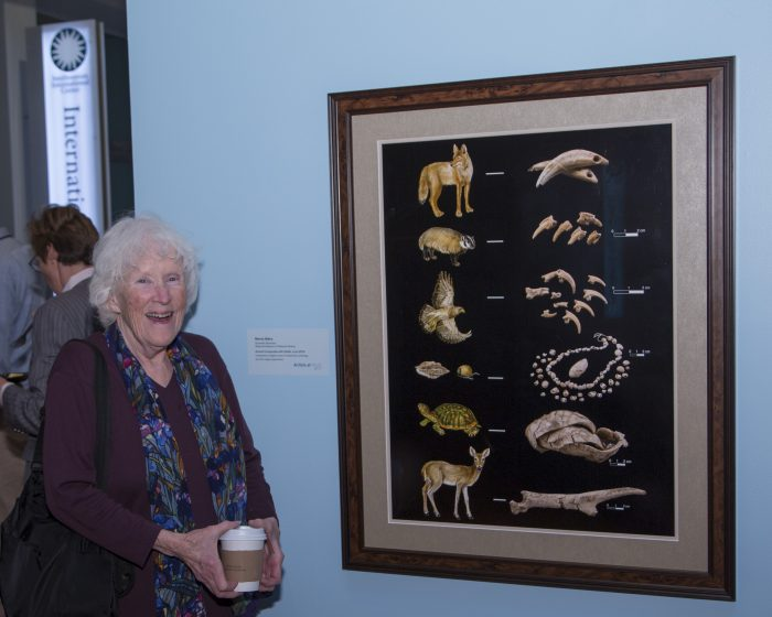 Artists stands next to her work in exhibition gallery