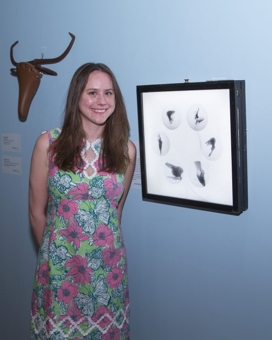 Artist standing with her work in exhbition gallery