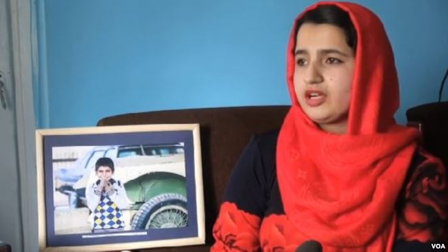 Young woman in hibab with framed photo of boy
