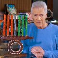 Trebeck in blue sweater poses next to folk art menorah