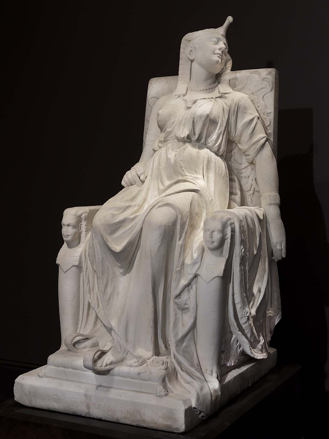 White marble sculpture of Cleopatra on throne
