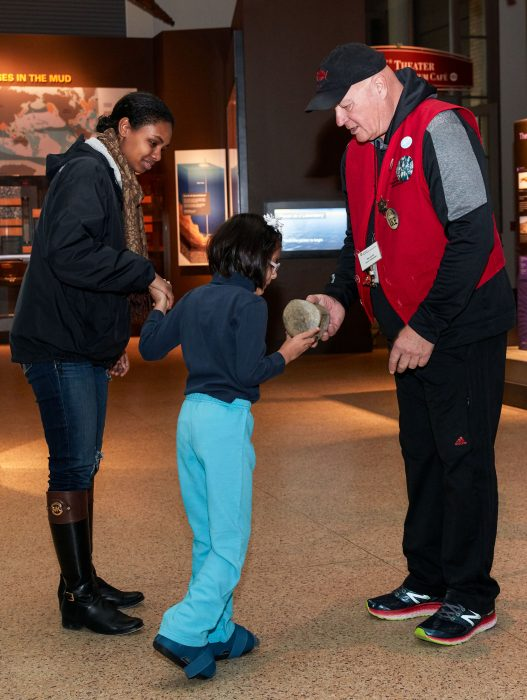 Child being gretted by NMNH volunteer