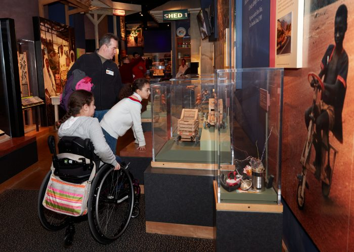 Child in wheelchair looks at exhibits