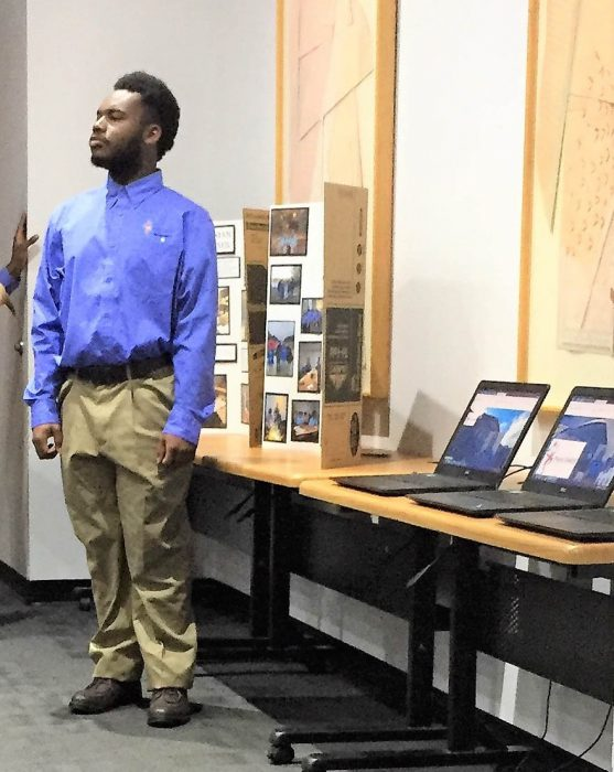 Young man stands next to display table at Project Search event