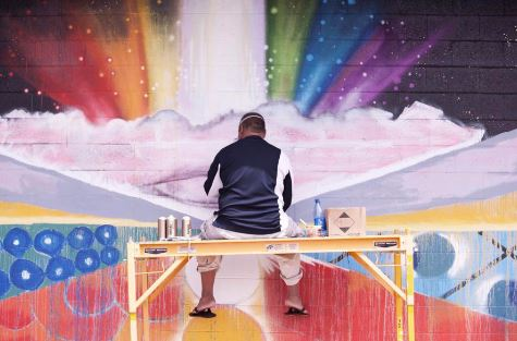 Artist with back to camera paints a mural