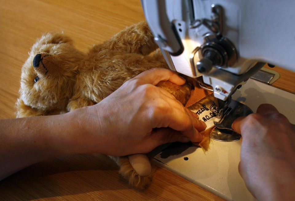 Close-up of someone using a sewing machine to repair a teddy bear