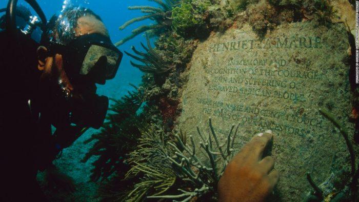 Scuba diver reads underwater inscription