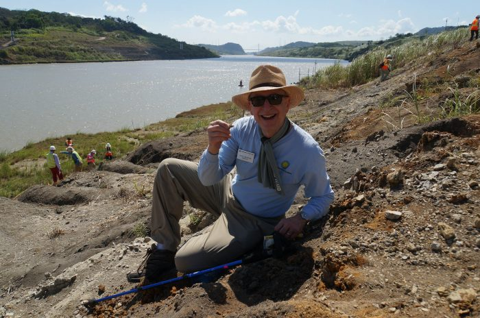 Skorton, wearing hat and sunglasses, smiles into camera and holds up a small fossil. Panama Canal in background
