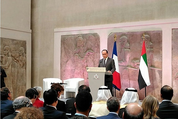 French president at podium addresses seated audience