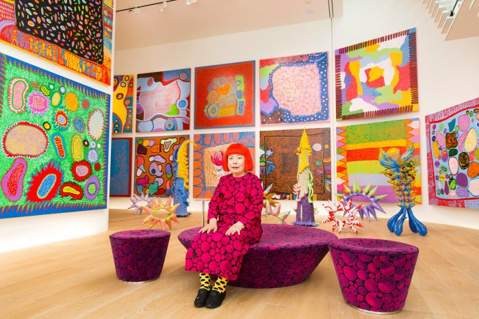 Artist in colorful dress and wig ingallery of bright paintings