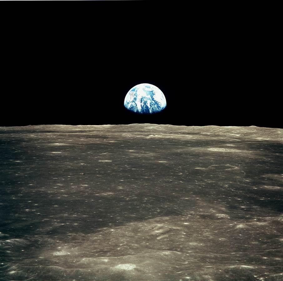 Earth rising over the moon's horizon