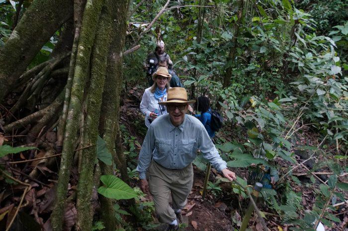 Dr Skorton in lead, Dr Davisson behind as they climb a forest trail.