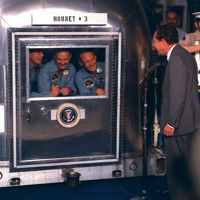Astronauts talkj to Nixon through capsule hatch