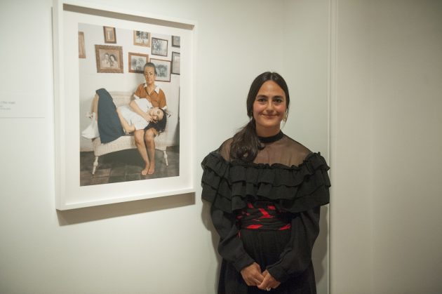 Artists stands next to her work in gallery
