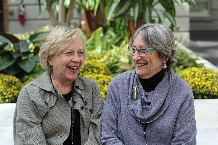Two older women sitting on bench laughing