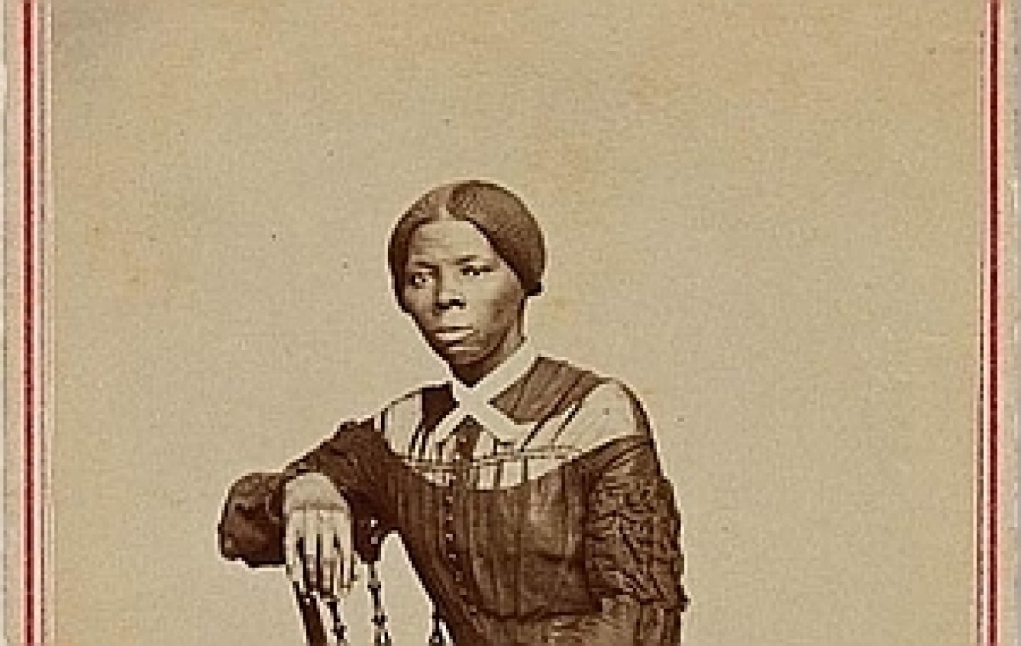 Sepia-toned photo of young Tubman leaning arm on chair