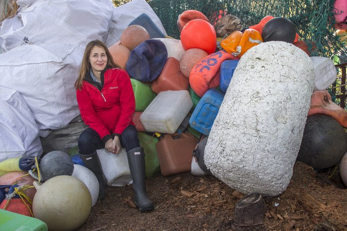 Madded in red jacket and boots sits among large pile of plastic objects
