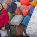 Cropped version of researcher Odile Maddon sitting with large pile of plastic objects on beach