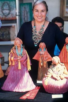 Abeyta wearing turquoise necklace with doll-like sculptures