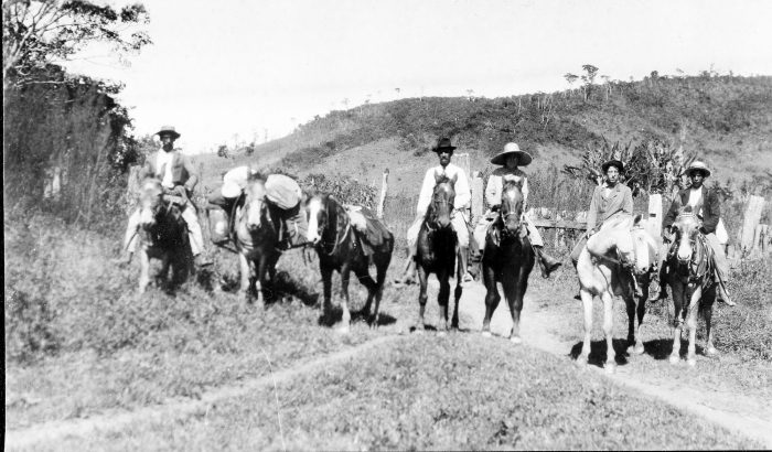 Photo of group of people on horseback with pack animals