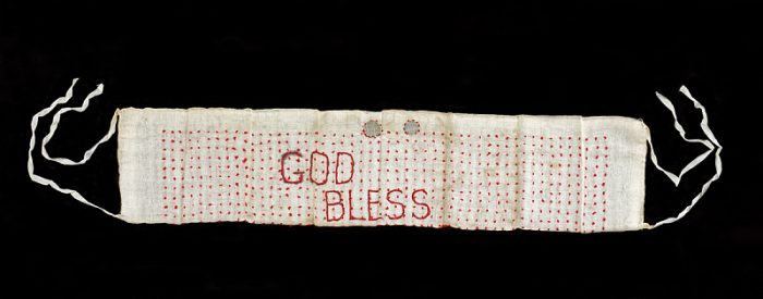 Hand-sewn sash with God Bless stiched on it