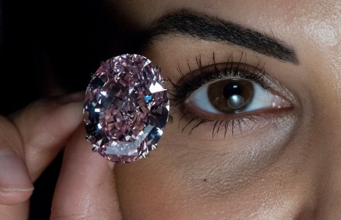 Woman hilding large pink diamond up to camera