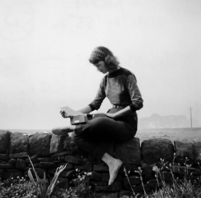 blurred black and white photo of young woman sitting on stone wall