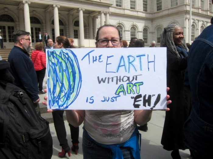 Protester holding sign saying the Earth without art is just eh