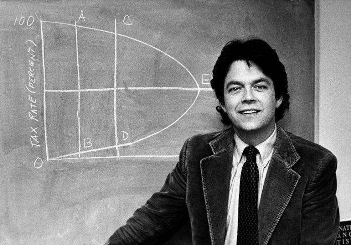 B&W photo of Laffer in corduroy jacket in front of blackboard