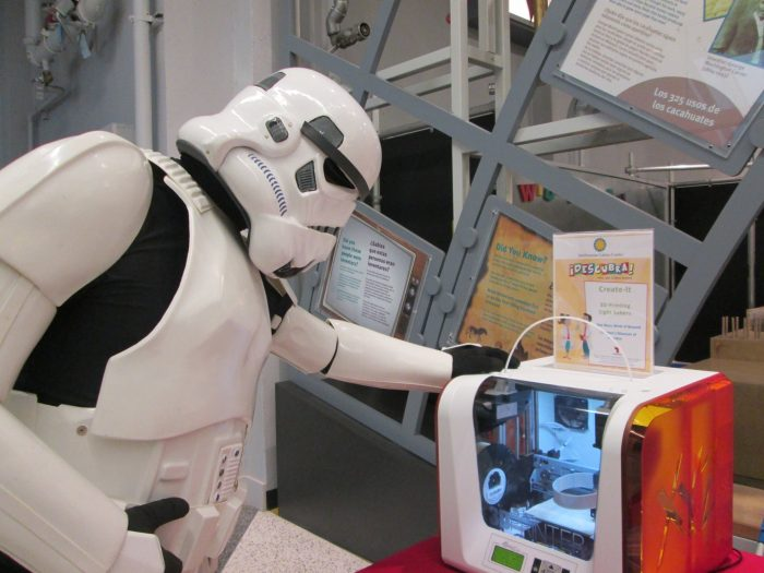 Person in stormtrooper costume looks at display