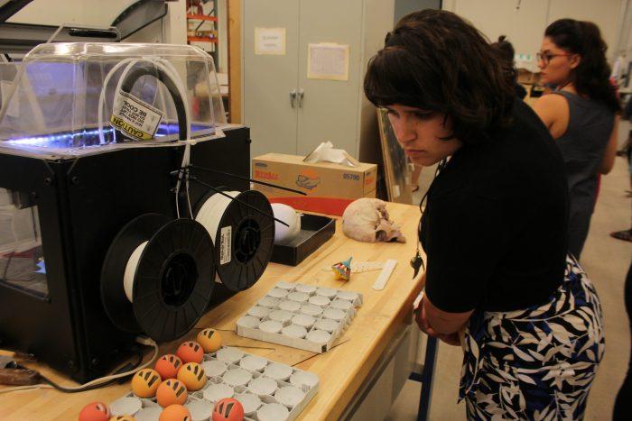Woman looks at printer display on table