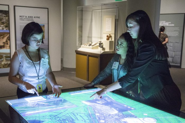 students gathered around lighted display table