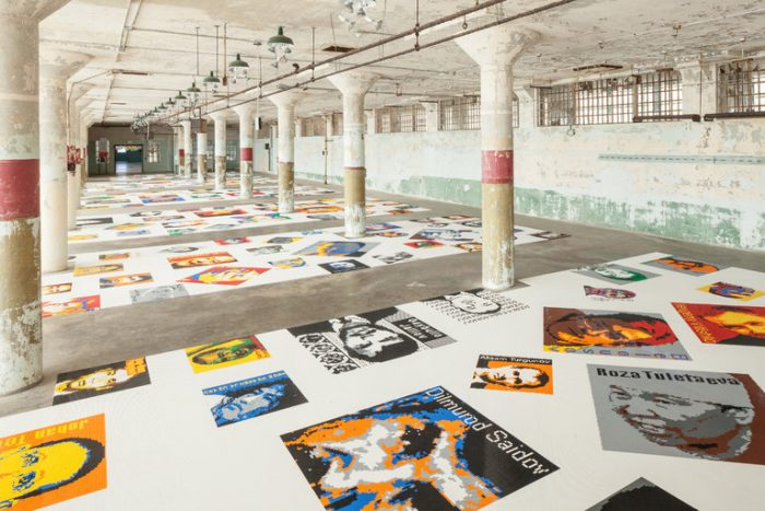 Series of abstract portraits displayed on floor