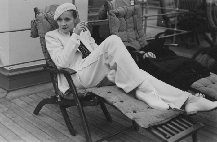 Acrtess in white suit and beret on deck chair