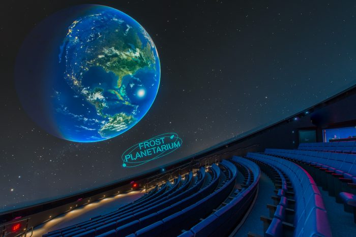 Tierd auditorium seats with screen displaying Earth
