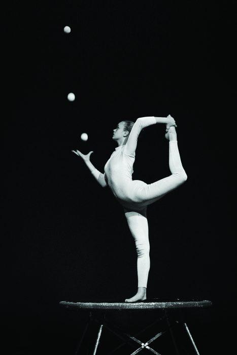 Young woman juggles while balancing on one leg